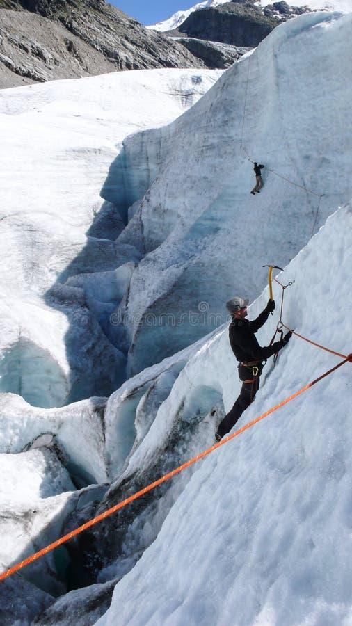 Två berghandbokkandidater som utbildar expertis för isyxa och reppå en glaciär i de schweiziska fjällängarna arkivfoto