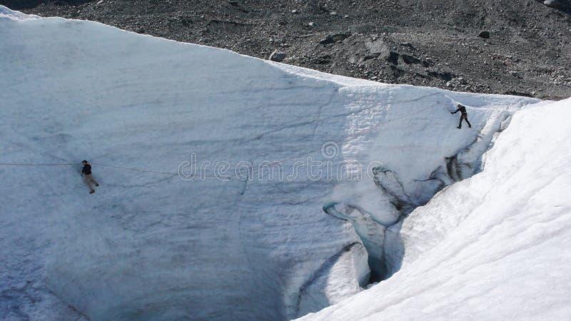 Två berghandbokkandidater som utbildar expertis för isyxa och reppå en glaciär i de schweiziska fjällängarna royaltyfri foto