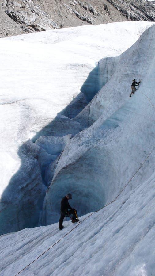 Två berghandbokkandidater som utbildar expertis för isyxa och reppå en glaciär i de schweiziska fjällängarna royaltyfria bilder