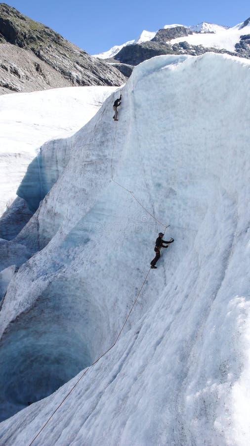 Två berghandbokkandidater som utbildar expertis för isyxa och reppå en glaciär i de schweiziska fjällängarna arkivfoton