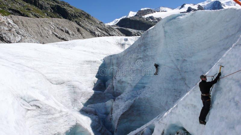 Två berghandbokkandidater som utbildar expertis för isyxa och reppå en glaciär i de schweiziska fjällängarna arkivbild