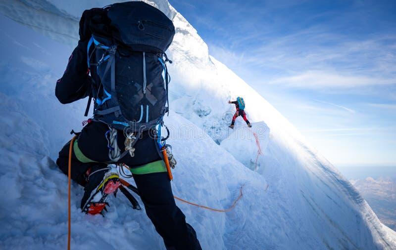 Två bergsbestigare klättrar extrema sportar för den branta glaciärissprickan, det Mont Blanc du Tacul berget, det Chamonix France arkivfoton