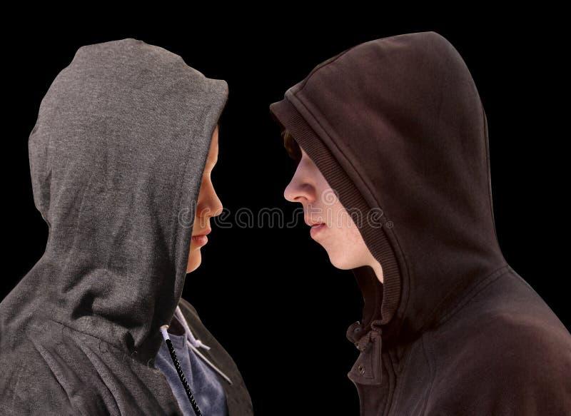 Två besvärade tonårs- pojkar med den svarta hoodien som framme står av de i profil som isolerades på svart bakgrund - materiel arkivbilder