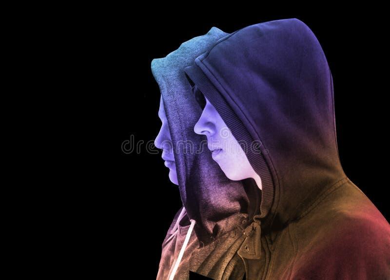 Två besvärade tonårs- pojkar med svart hoodieanseende bredvid de i profil som isolerades på svart bakgrund idérikt färgrikt arkivbild