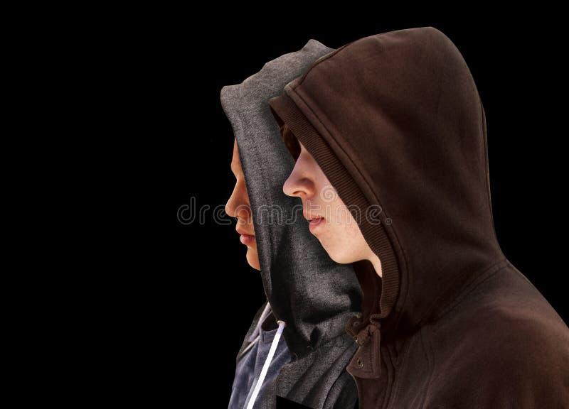 Två besvärade tonårs- pojkar med svart hoodieanseende bredvid de i profil som isolerades på svart bakgrund - materiel royaltyfria foton