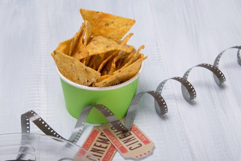 Två biljetter till bion, under en hink av nachos och det uppackade bandet för film arkivfoton