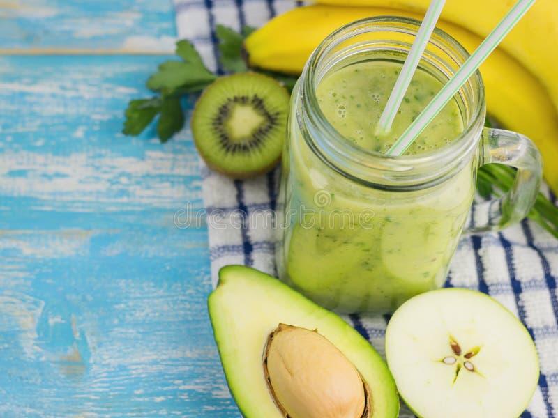 Två blåa coctailsugrör i en koppsmoothie med avokadot, kiwin och bananen övre sikt Banta vegetarisk mat Rå foods royaltyfri fotografi