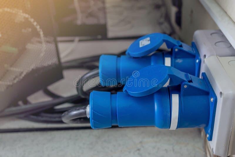 Två blåa hög-spänning makthåligheter och proppar pluggas in i serverdatoren arkivfoton