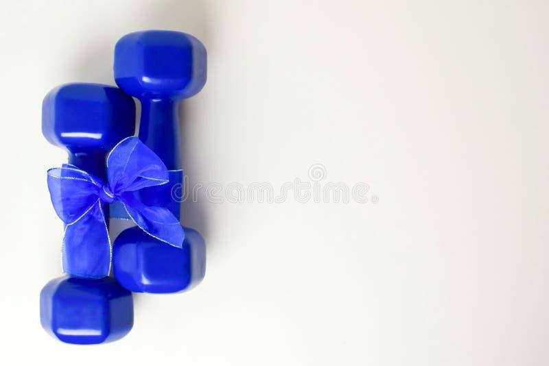 Två blåa hantlar med gåvapilbågen på vit bakgrund, sport och sunt begrepp arkivbild