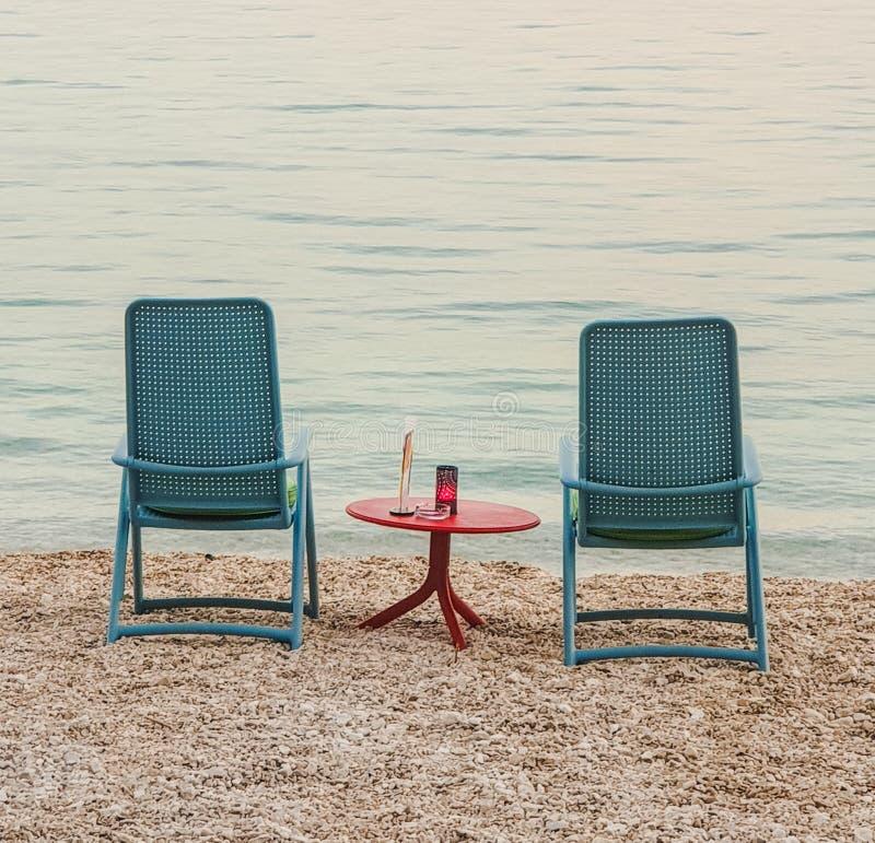 Två blåa stolar med en röd tabell i det mellersta anseendet på Pebblet Beach av Adriatiskt havet i sommar på en varm afton royaltyfri bild