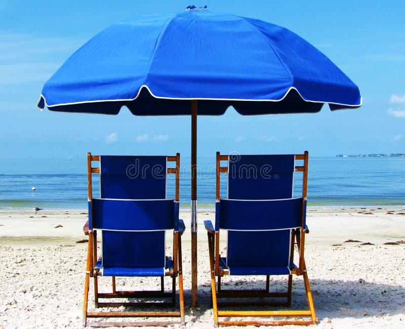 Två blåa strandstolar och paraply på stranden royaltyfria foton