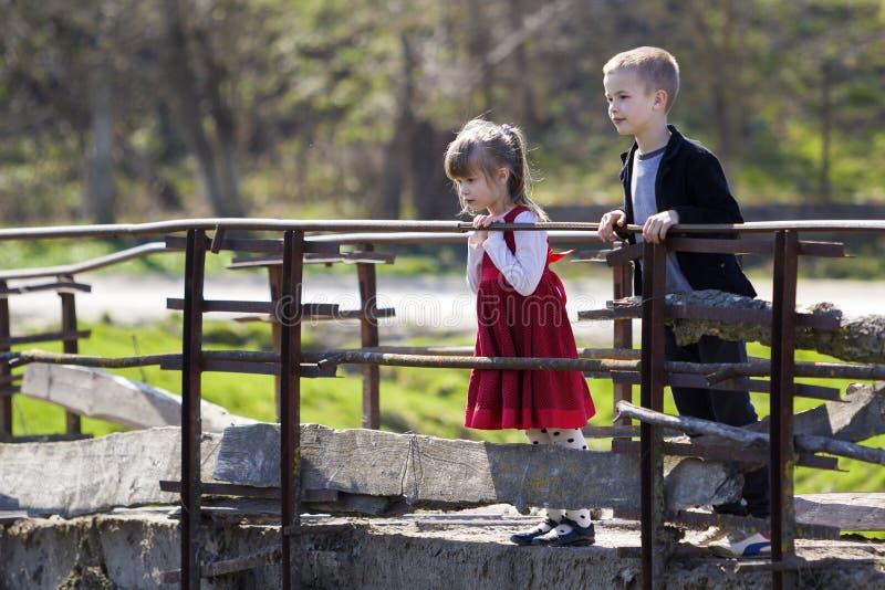 Två blonda nätta barn, liten långhårig flicka och gullig pojkebenägenhet på träräcke av den gamla bron som ser fast beslutsamt ne royaltyfri fotografi
