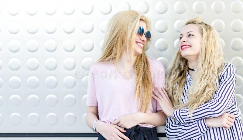 två blonda vänner för kvinnastudenter som skrattar genom att använda mobiltelefonen och minnestavlan arkivbild