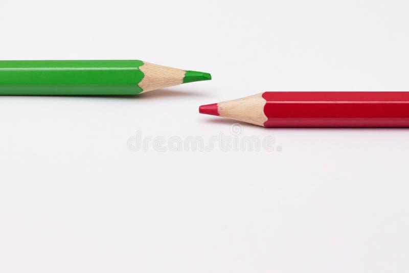 Två blyertspennor av grönt och rött, symboliserar opposite_en fotografering för bildbyråer