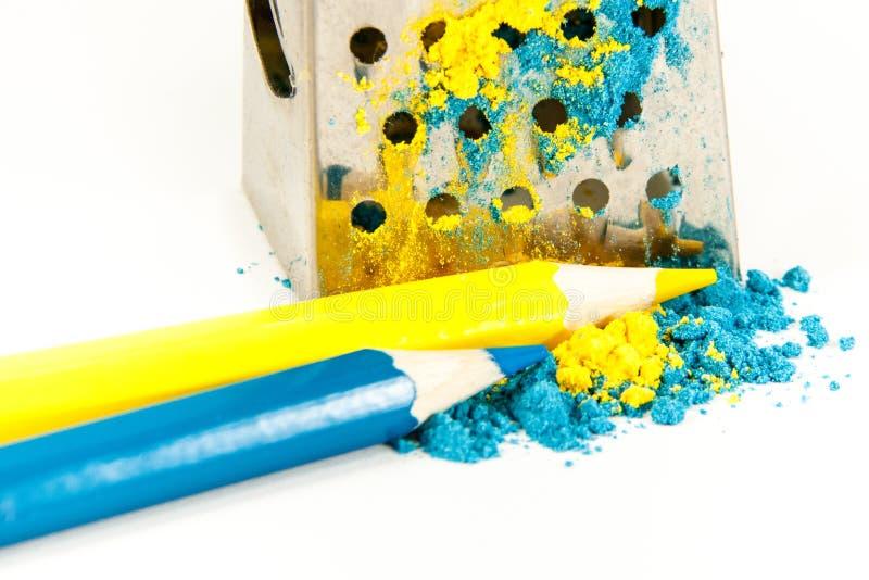 Två blyertspennor guling och blåttlögn nära rivjärnet fotografering för bildbyråer