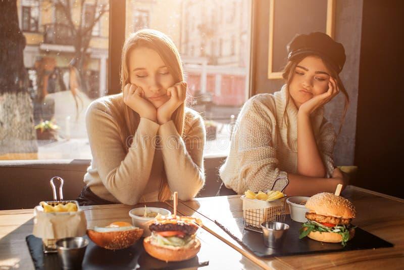Två borrade unga kvinnor sitter på tabellen och blicken på mat De håller händer under hakan Modeller är i kafé Sun är glänsande royaltyfri bild