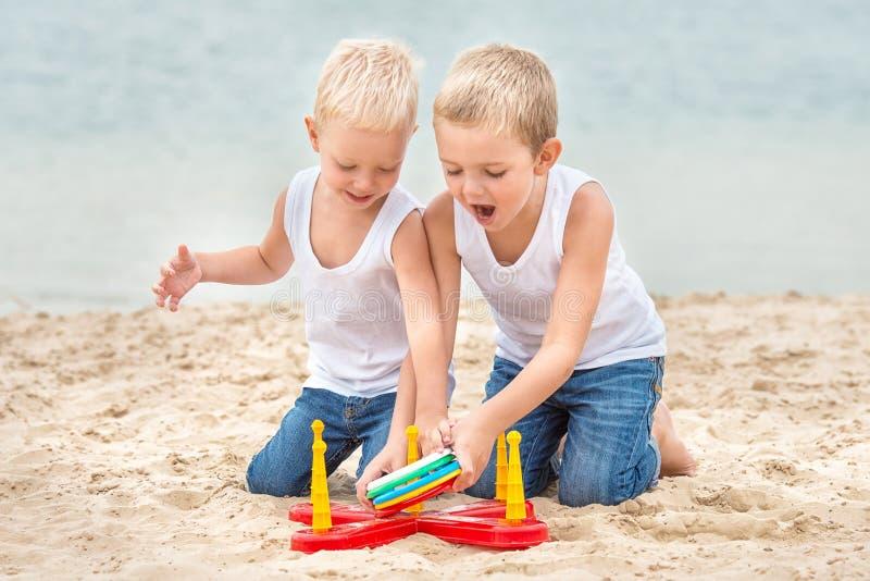 Två bröder är gå och spela på stranden Leken är ett cirkeldugg fotografering för bildbyråer