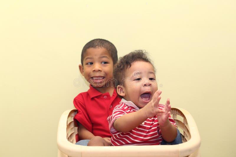 Två bröder av blandat lopp Fokusen behandla som ett barn framtill royaltyfri fotografi