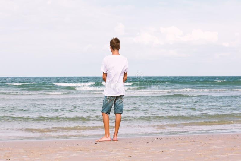 Två bröder av en tonåring som spelar på havet, kamratskapnollan royaltyfria bilder