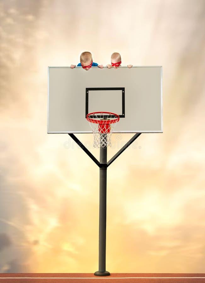 Två bröder i dräkt av superheroes sitter på en basketcirkel och håller ögonen på leken fotografering för bildbyråer