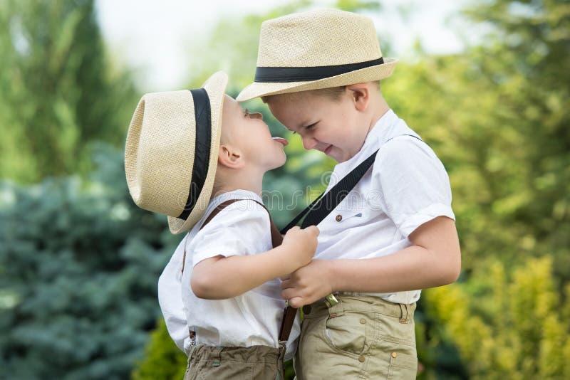 Två bröder i sugrörhattar som spelar och har gyckel arkivbild