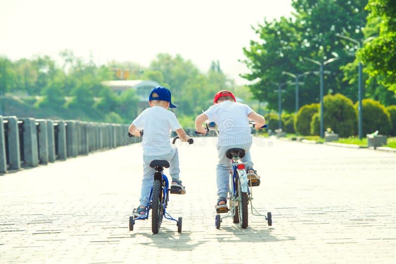 Två bröder rider en cykel på stranden arkivbilder