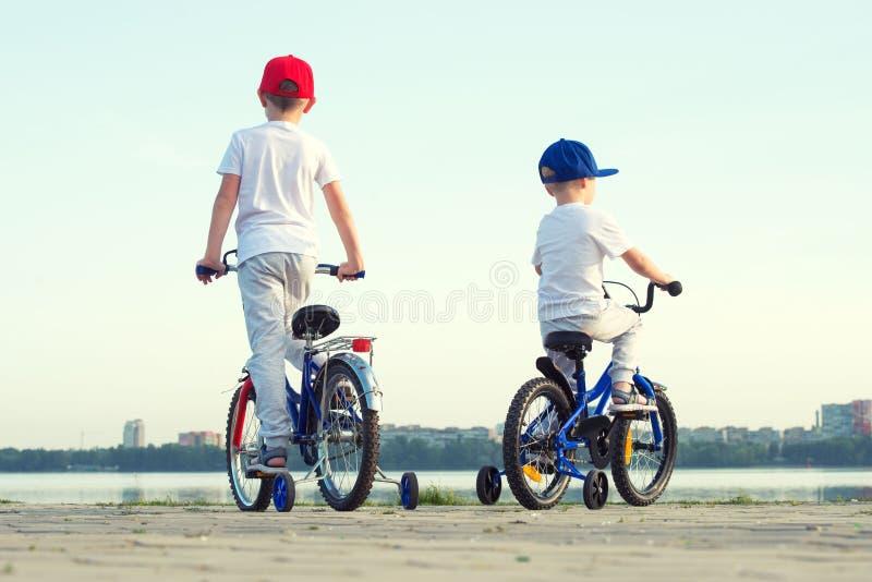 Två bröder rider en cykel på stranden arkivbild
