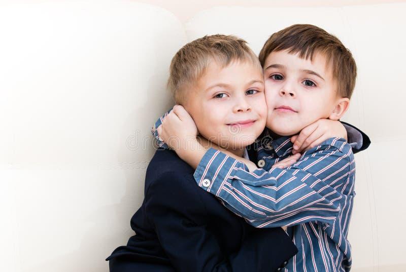 Två bröder som kelar på soffan arkivbilder