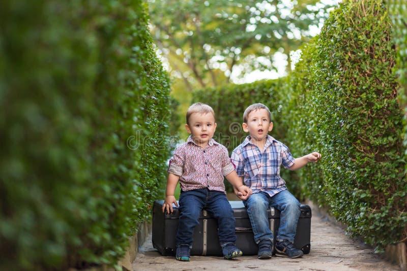 Två bröder som sitter på en resväska arkivfoto