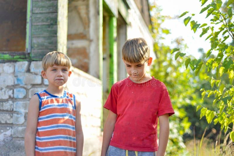Två bröder står i närheten av ett bränt hus, som förlorade sina hem till följd av fientligheter och naturkatastrofer royaltyfri fotografi