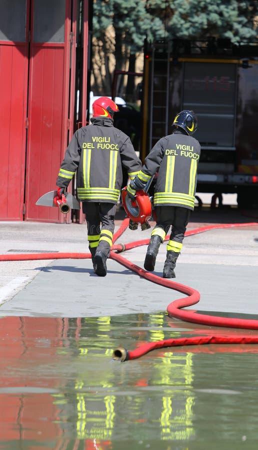 Två brandmän bär vattenpost- och slangrören arkivfoto