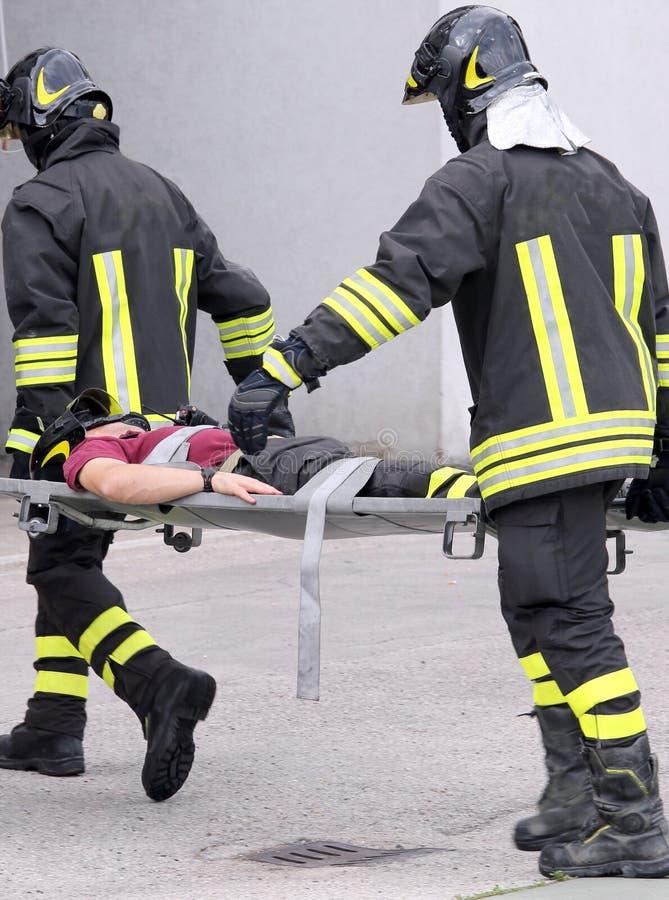 Två brandmän bar som sårades bort på bårar arkivbilder