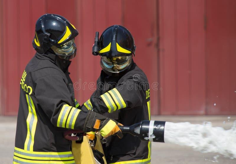 Två brandmän i handling med skum royaltyfri fotografi