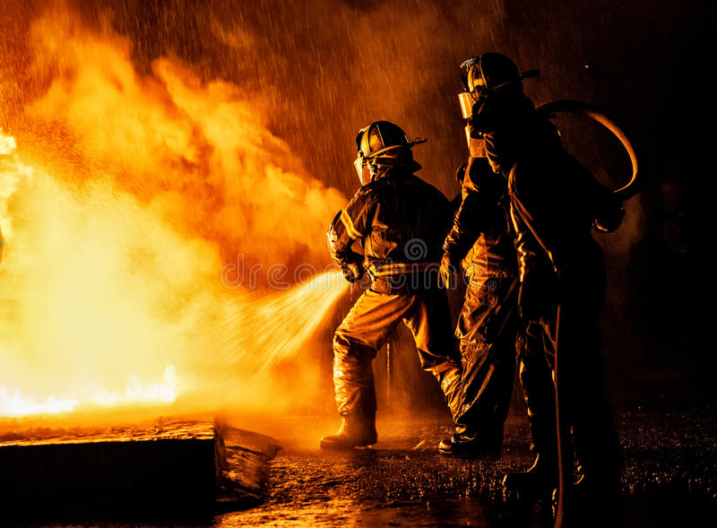 Två brandmän som slåss brand med en slang och ett vatten royaltyfri foto