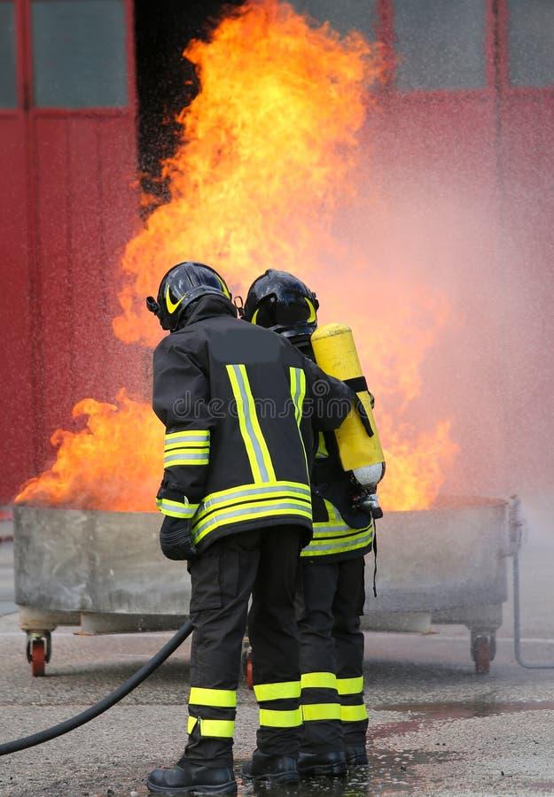 Två brandmän under övningen med en full brand för behållare och t arkivbilder