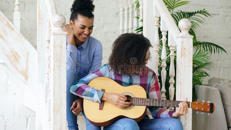 Två brasilianska lockiga flickasistres som sitter på trappa, och övning att spela den akustiska gitarren Vänner har roligt och sj arkivbilder