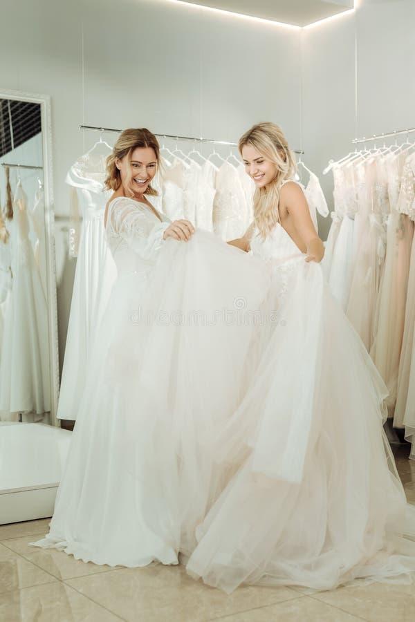 Två brudar som ser klänningarna av de arkivfoton