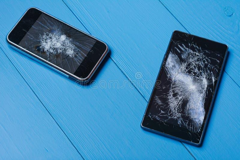 Två brutna mobiltelefoner på den målade trätabellen royaltyfria bilder