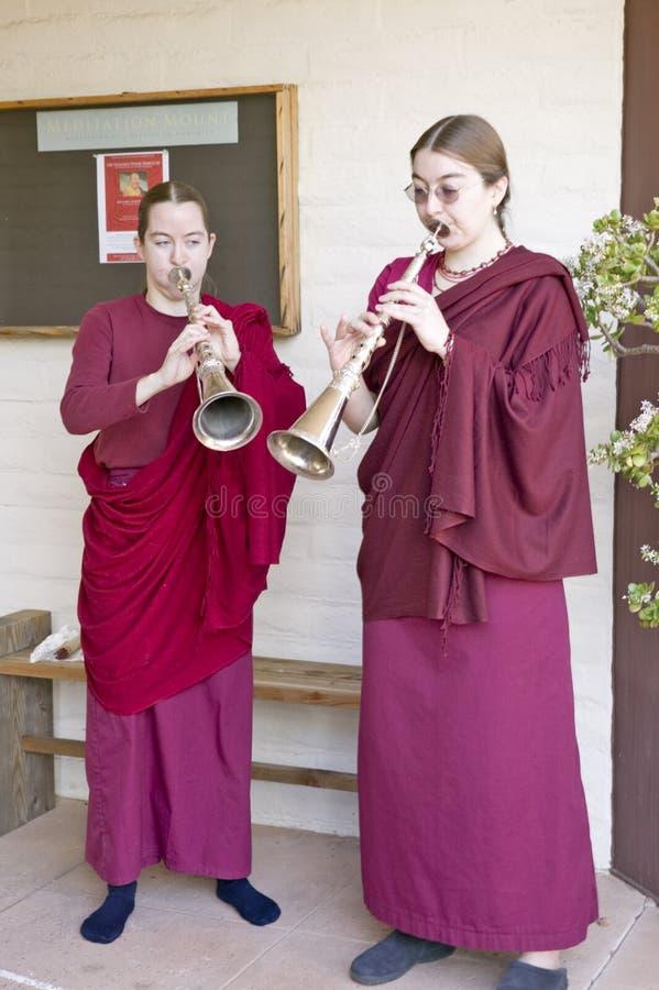 Två buddistiska nunnor blåser horn på buddistisk ceremoni för Amitabha bemyndigande, meditationmontering i Ojai, CA royaltyfri bild