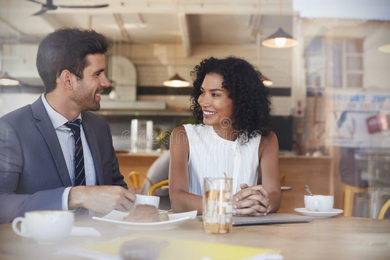 Två Businesspeople möter i coffee shop som skjutas till och med fönster arkivbild