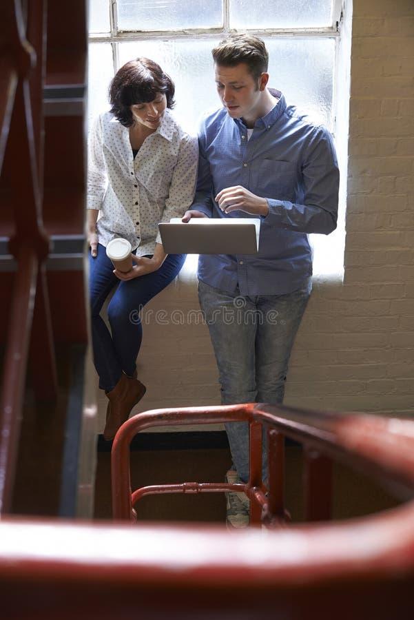 Två Businesspeople som har informellt möte på kontorstrappa royaltyfri fotografi