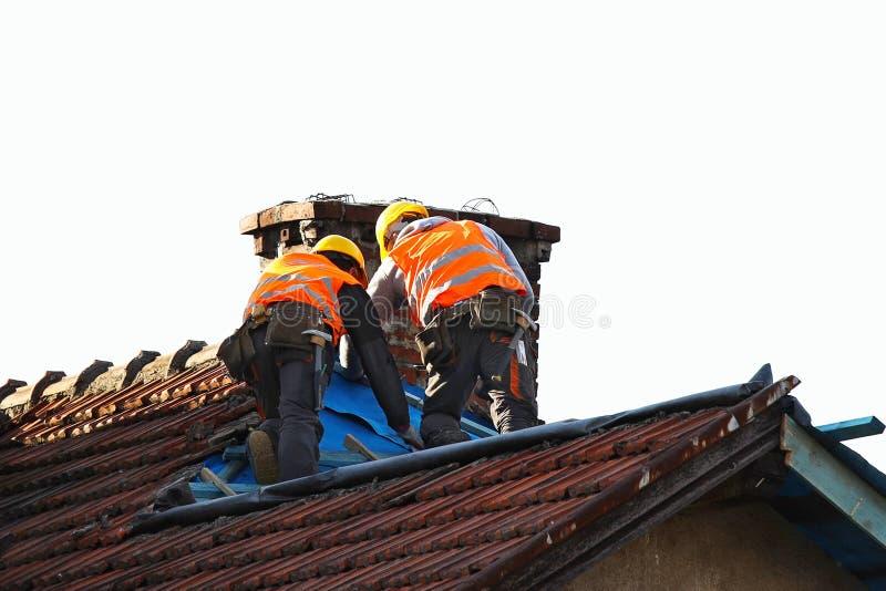 Två byggmästare i arbetekläder som fixar ett gammalt belagt med tegel tak på en byggnad Byggnation på höjd på ett vitt arkivfoton