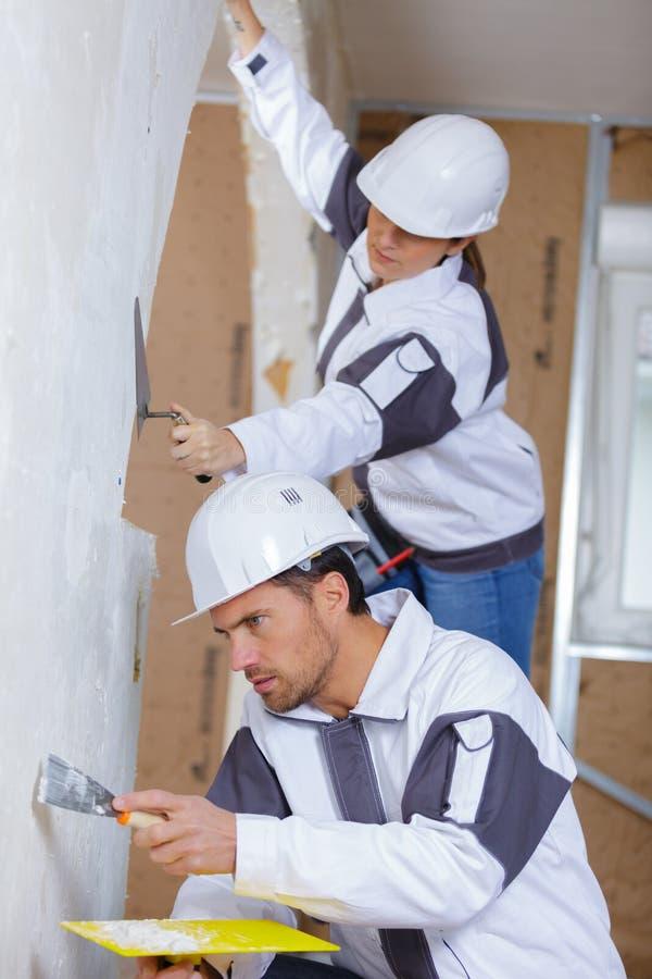Två byggmästare i hardhats och overaller med spateln som reparerar rum royaltyfri bild