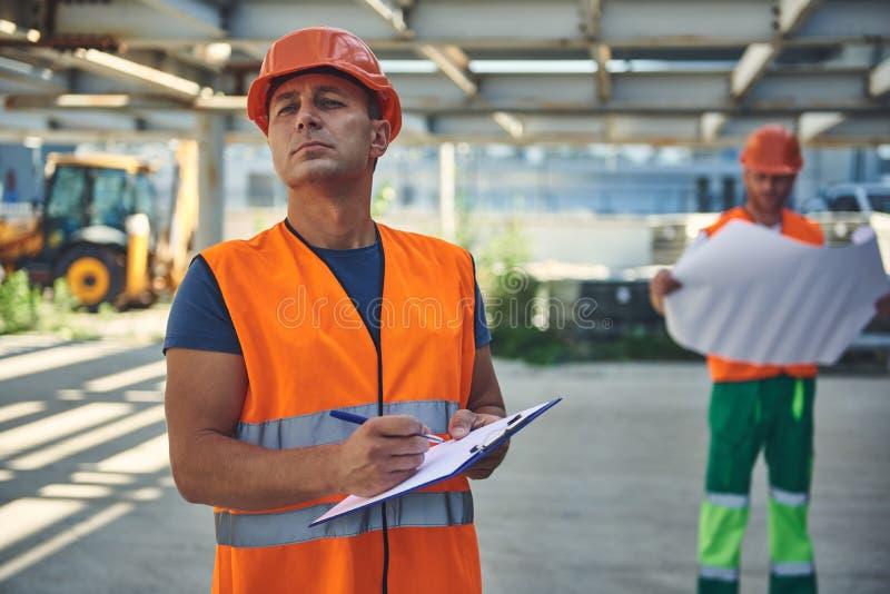 Två byggmästare i orange västar arbetar på konstruktionsplatsen arkivfoton