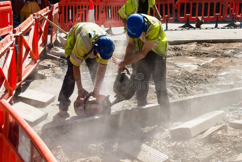 Två byggmästare som klipper vått klipp för betong arkivfoto
