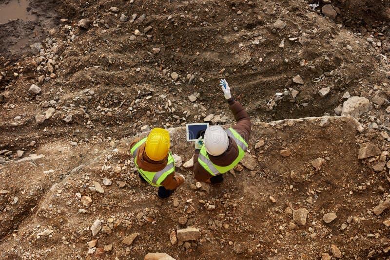 Två byggnadsarbetare som kontrollerar platsen royaltyfri bild