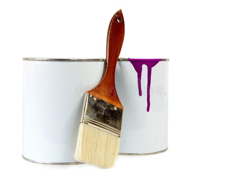 Två cans av målarfärg och en borste fotografering för bildbyråer