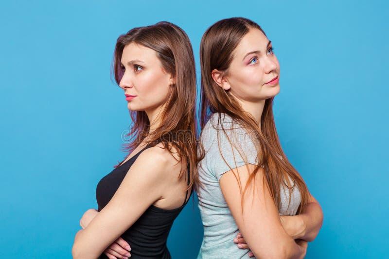 Två caucasian attraktiva unga kvinnor står tillbaka för att dra tillbaka, med korsade händer royaltyfria bilder