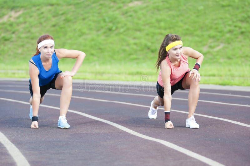 Två Caucasian idrottskvinnor i professionelln Sportsgear som står förberedd för att köra på sportmötesplats utomhus royaltyfria bilder