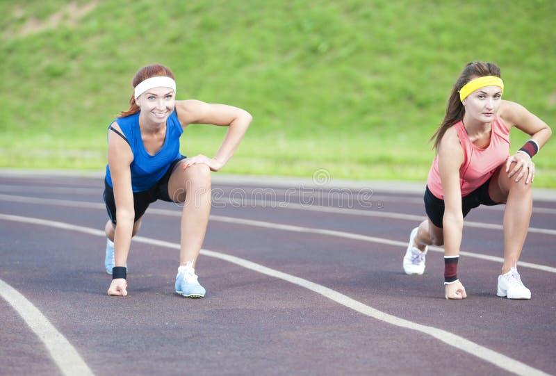 Två Caucasian idrottskvinnor som utomhus står före spring på sportmötesplats royaltyfria foton
